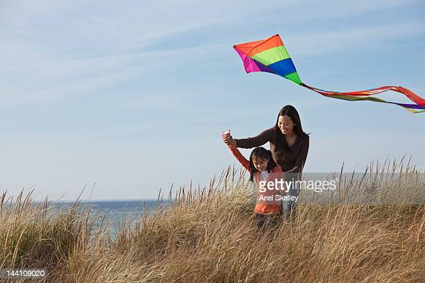 Asian mother and daughter flying kite on beach