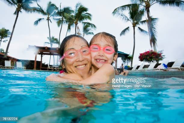 Asian mother and daughter hugging in swimming pool