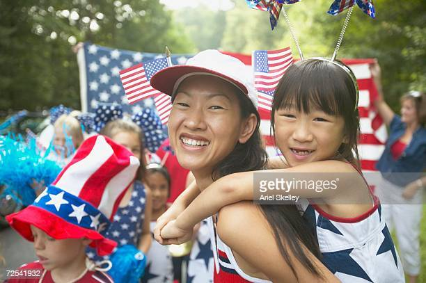 asian mother and daughter in fourth of july parade - independence day stock pictures, royalty-free photos & images
