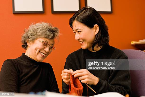 Asian mother and daughter knitting