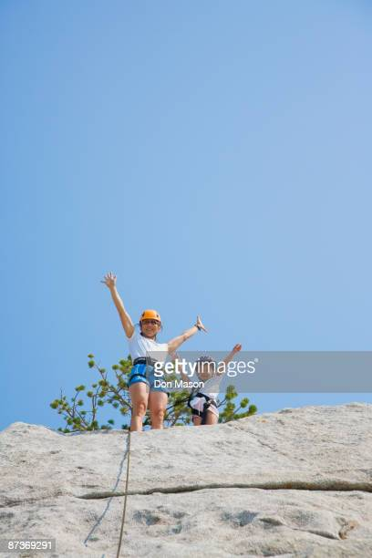 Asian mother and daughter rock climbing