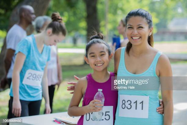 asian mother and daughter smile for the camera before the marathon begins - marathon stock pictures, royalty-free photos & images