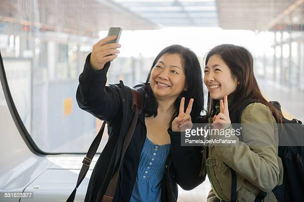 Asian Mother and Daughter Taking Selfie on Train