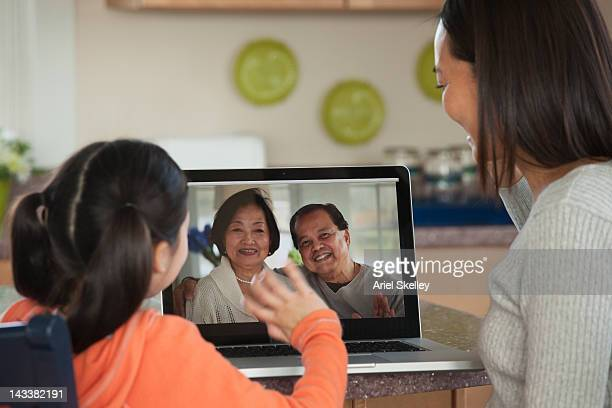 Asian mother and daughter talking to family on laptop