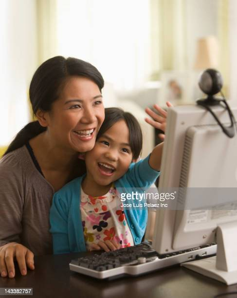 asian mother and daughter using webcam on computer - mother daughter webcam stock-fotos und bilder