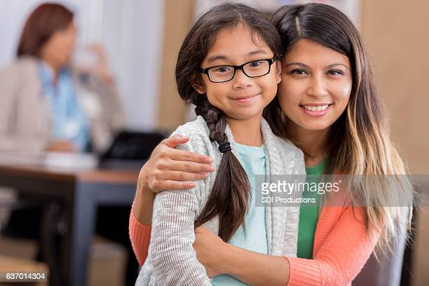 Asian mother and daughter wait in hospital waiting room