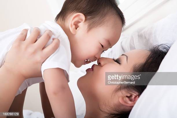Asian mother and son bedroom portrait