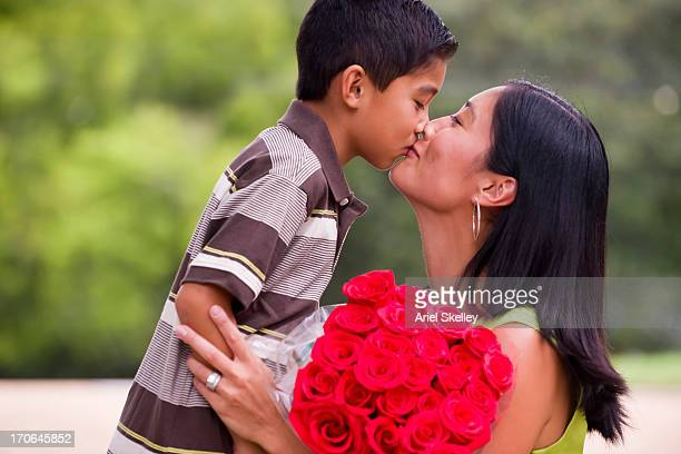 Asian mother and son kissing