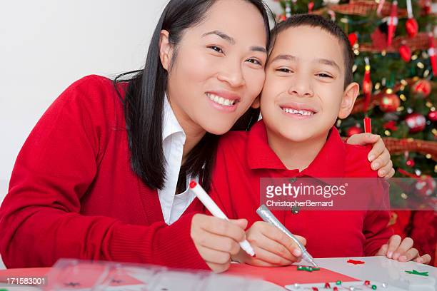 Asian mother and son making christmas cards