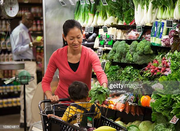 Asian mother and son shopping for fresh vegetables