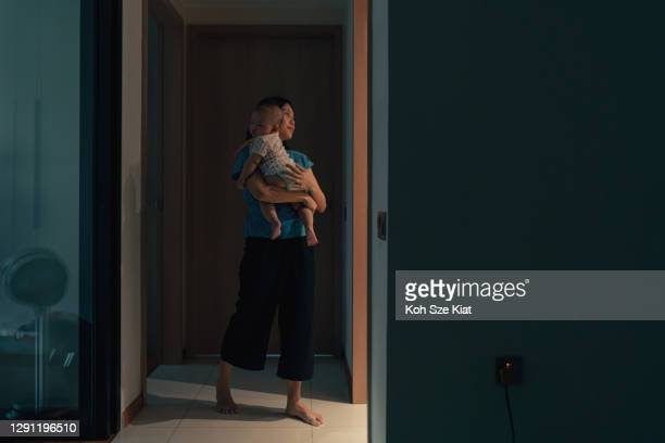 asian mother attending to the newborn's needs in the middle of the night - midnight stock pictures, royalty-free photos & images