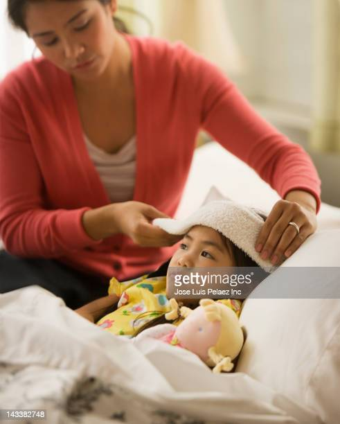 Asian mother comforting sick daughter