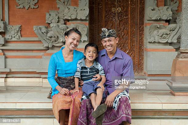 Asian mother, father and son smiling outside ornate building
