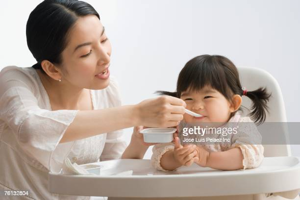 Asian mother feeding baby daughter