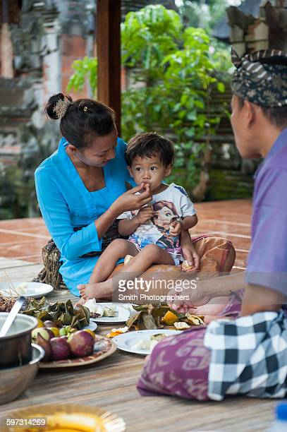 Asian mother feeding son on woven mat