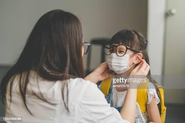 アジアの母親は、保護コロナウイルスの流行のためのフェイスマスクを身に着けている彼女の娘を助けます - 新学期 ストックフォトと画像