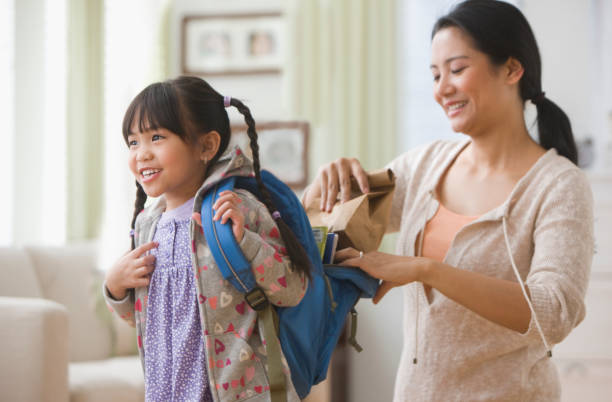asian mother helping daughter get ready for school - preparation stock pictures, royalty-free photos & images