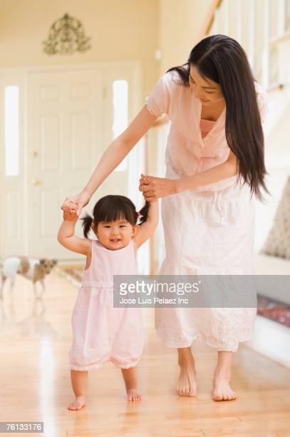 Asian mother helping daughter walk
