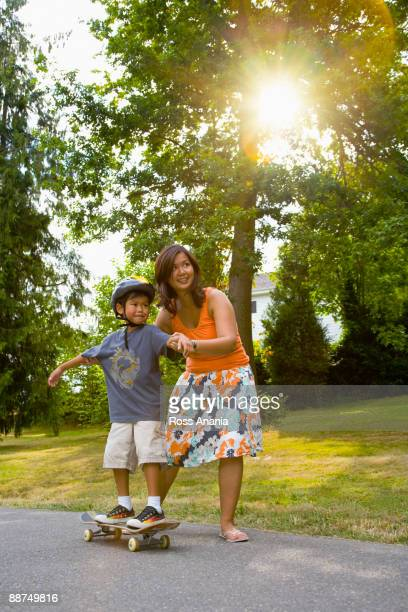 Asian mother helping son learn to skateboard