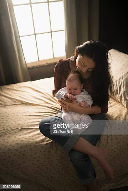 Asian mother holding baby on bed