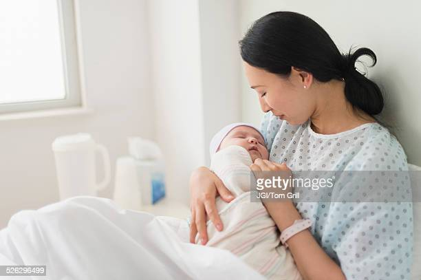 Asian mother holding newborn baby in hospital bed