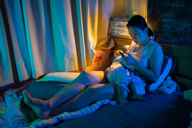 Asian mother negative emotion  Breastfeeding daughter and using phone on the bed late night  postpartum concept