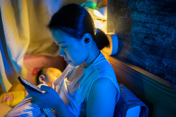 Asian mother positive emotion  Breastfeeding daughter and using phone with wireless in-ear headphone  on the bed late night  postpartum concept