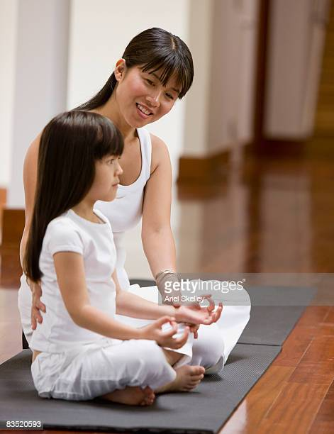 Asian mother teaching daughter yoga