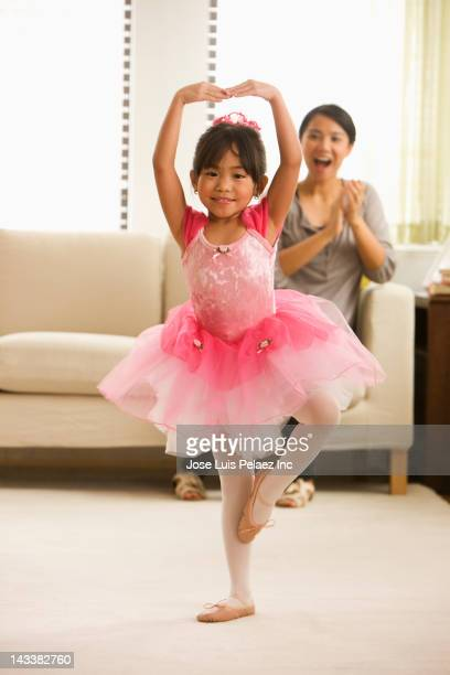 Asian mother watching daughter ballet dancing