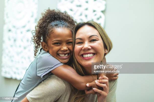 asian mother with daughter of mixed chinese and african american ethnicity at home indoors posing playfully for portraits smiling and being silly - mixed race person stock pictures, royalty-free photos & images