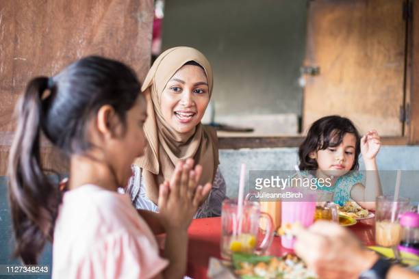 asian mother with her family at lunch, watches her daughter clapping her hands - malaysian culture stock pictures, royalty-free photos & images