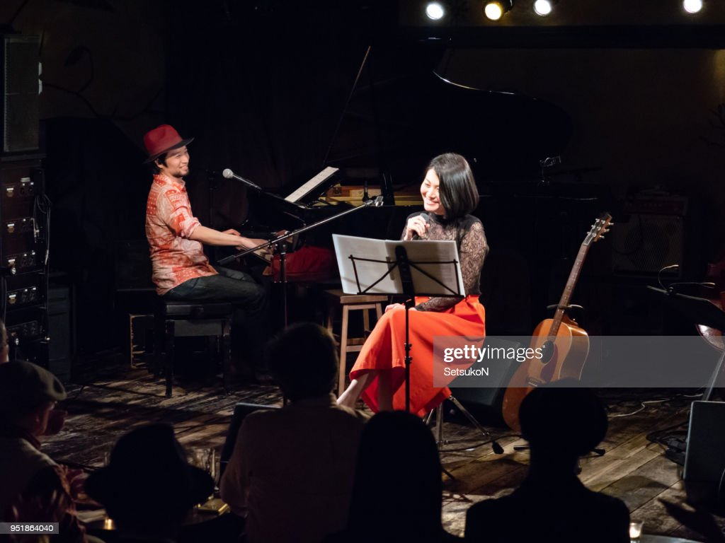 Asian musicians, pianist and guitarist, performing on stage : Stock Photo