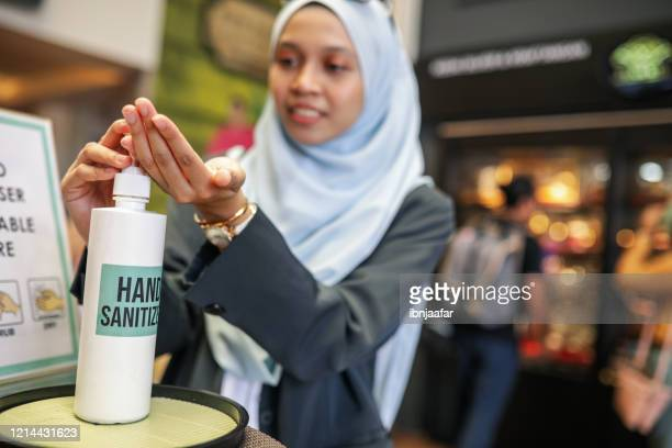 asian muslim corporate women washing hand using sanitiser - station stock pictures, royalty-free photos & images
