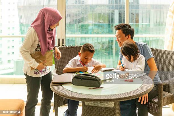 asian muslim family doing homework together - modest clothing stock pictures, royalty-free photos & images