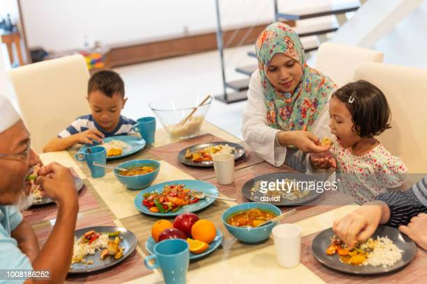Asian Muslim Family Eating Dinner Together