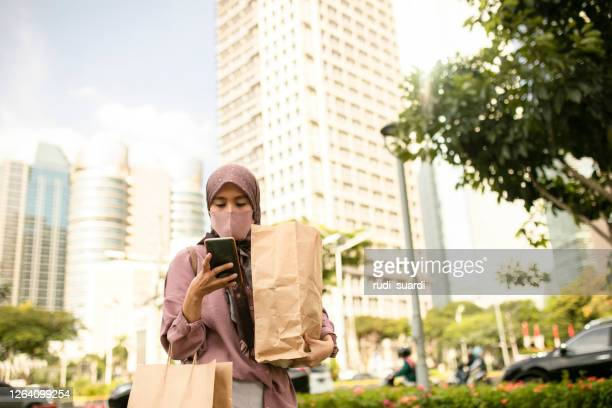 asian muslim woman using phone when walking on the street - jakarta stock pictures, royalty-free photos & images