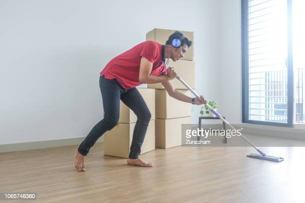 Asian muslim young man dancing and wiping the floor at his new house while moving in.