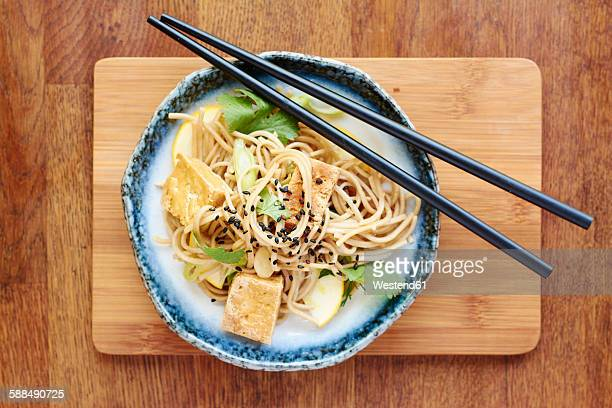 asian noodle salad with soba noodles, tofu, green onions, yellow zucchini and coriander, garnished with black sesame seeds - soba stock pictures, royalty-free photos & images