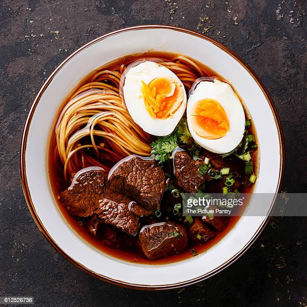 Asian noodles in broth with slow cooked Beef and Egg on dark background close up