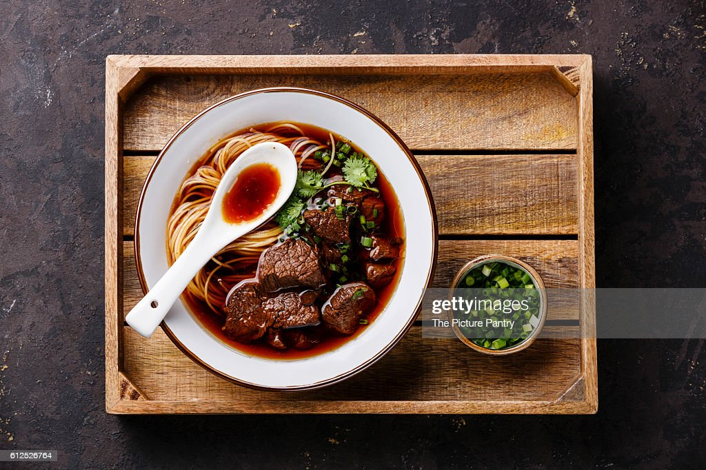 Asian noodles in broth with slow cooked Beef in wooden tray on dark background : Stock-Foto