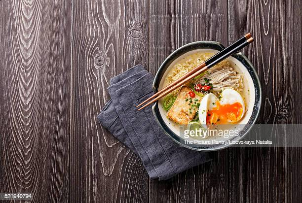 Asian noodles with egg, tofu and enoki in bowl on gray wooden ba