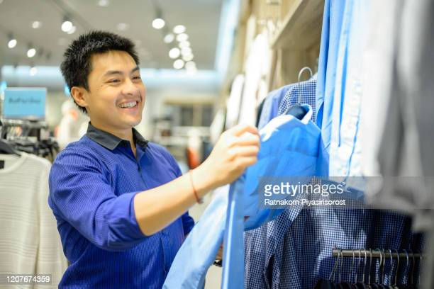 asian office worker male choosing clothes in clothing store at shopping mall, compare the differences between shirts, fashion, style and consumerism concept - タイ人 ストックフォトと画像