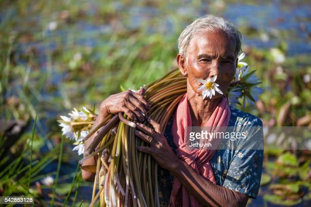 Asian Old women holding water lilies on shoulder