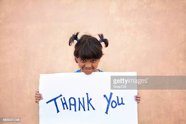 Asian or Latin child holds 'Thank You' sign outdoors.