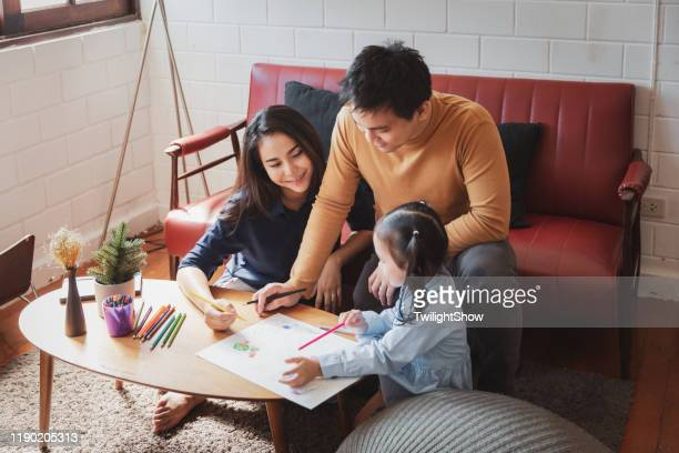 asian parent family with girl child and teaching child how to draw at home with happiness - family at home stock pictures, royalty-free photos & images