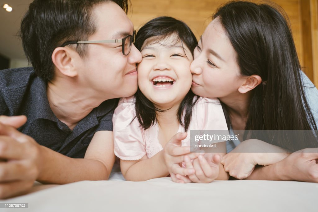 Asian Parents kissing their little daughter on both cheeks. family portrait. : Stock Photo