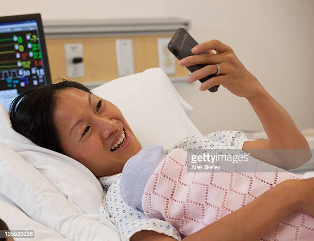 Asian patient in hospital bed looking at cell phone