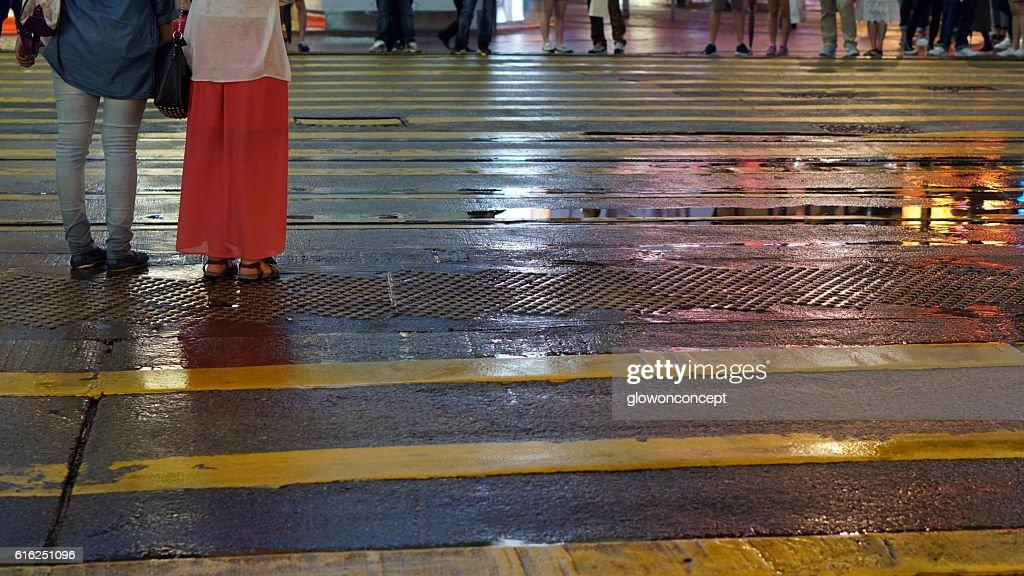 Asian people cross wet street with neon light reflection : Foto de stock