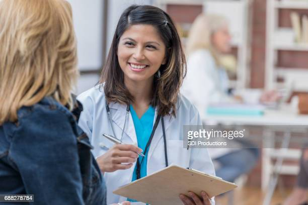 asian physician consults with female patient - emergency medicine stock pictures, royalty-free photos & images