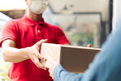 Asian postman, deliveryman wearing mask carry small box deliver to customer in front of door at home. Man wearing mask prevent covid19, corana virus affection outbreak. Social distancing work concept.
